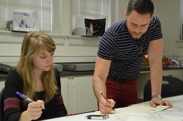 Brian Taylor works with a student on her design